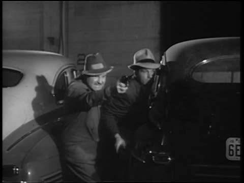 B/W 1930s/40s two men between two cars shooting pistols alternately