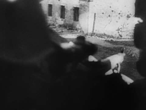 1940s black and white long shot German soldier shot by Russian sniper / dropping gun and falling to ground / Leningrad