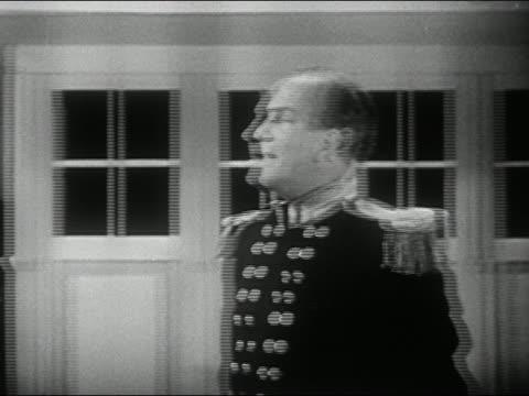 1940s black and white medium shot cameraman operating TV camera in studio / pan actors in period costume / zoom out set