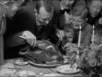 1940s black and white medium shot man carving turkey surrounded family members / pan holding up first slice