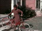 1940s PAN Black girl pushes bicycle down stairs to sidewalk / man helps her / home movie