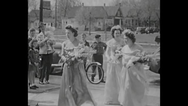 1940s  Bride arrives at church in vintage car with father / wedding guests wait outside of church / bridemaids arrive to church