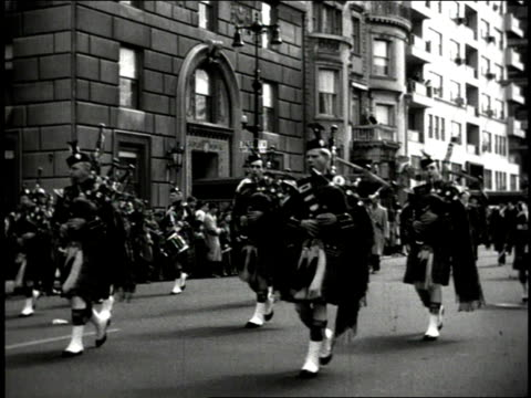 1940s B/W Highland marching band parading down city street