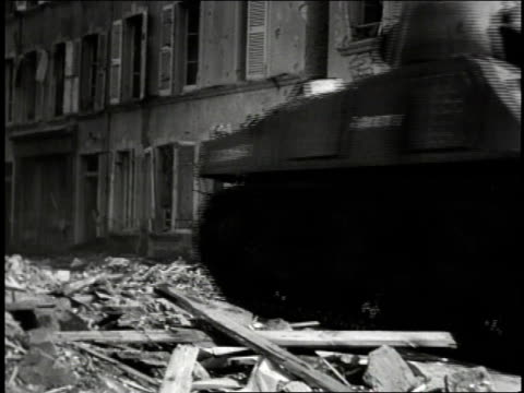 1940s B/W US Army Sherman tanks driving through streets of a bombed city over a Wehrmacht helmet / European Theater of Operations