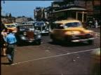1940s cars on city street past trolleys + pedestrians / Coney Island, New York