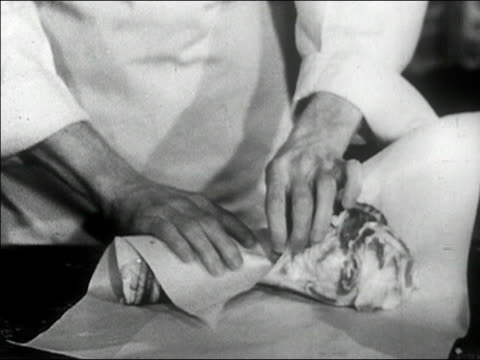 1940s Close up butcher wraps up piece of meat with money/ AUDIO