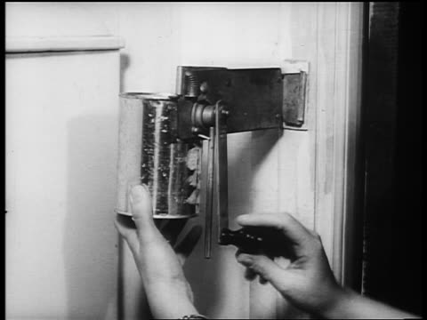B/W 1940s close up hand of woman opening tin can with wall-mounted opener / newsreel