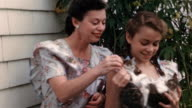1940s close up mother and daughter wearing matching dresses + playing with kittens