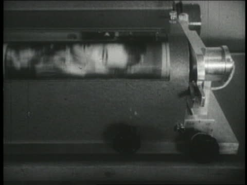 B/W 1940s close up spinning photo being transmitted by early fax machine