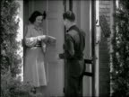 B/W 1940s delivery man handing woman package at front door / she tips him