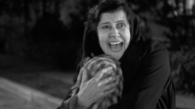 1940s dolly shot zoom in hooded woman screaming and holding child in blanket to chest at night