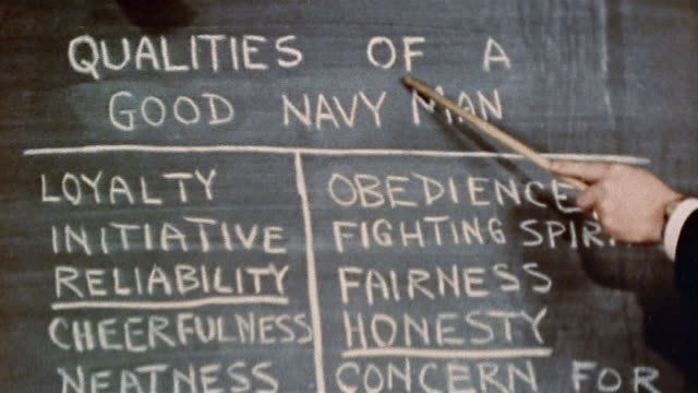 1940s hand pointing at 'QUALITIES OF A GOOD NAVY MAN' listed on chalkboard at naval training center