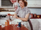 1940s housewife pours fruit salad in gelatin from bowl into can and puts it in refrigerator / indust.