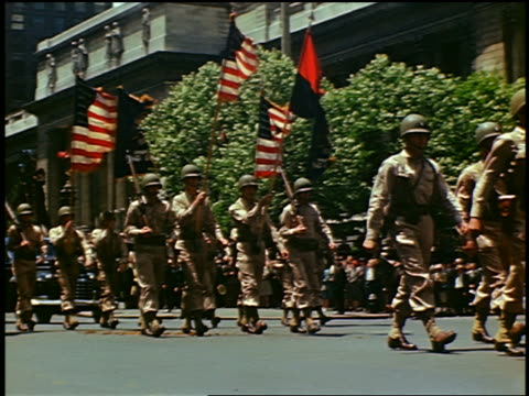 1940s low angle Army Guard marching with flags in parade on Fifth Avenue / New York City