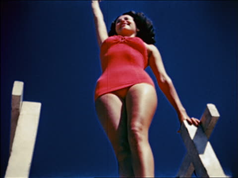 1940s low angle woman in swimsuit standing on dock waving / travelogue