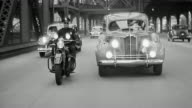 B/W 1940s REAR car point of view driving on bridge with motorcycle officer escorting ambulance