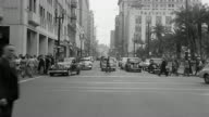 B/W 1940s REAR car point of view driving on city street with people crossing + cars turning / Los Angeles