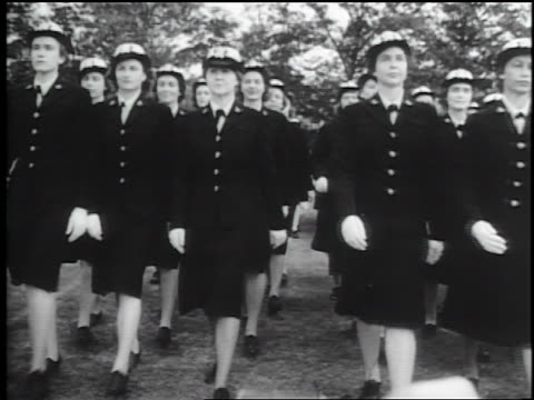 B/W 1940s rows of WAVES in uniform marching in formation toward camera outdoors / documentary