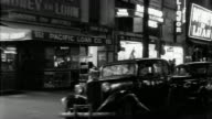 B/W 1940s SIDE car point of view driving past stores + burlesque theaters at night / Los Angeles
