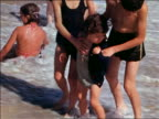 1940s three children in swimsuits stand in surf on beach / home movie