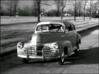 B/W 1940s tracking shot couple driving car on country road