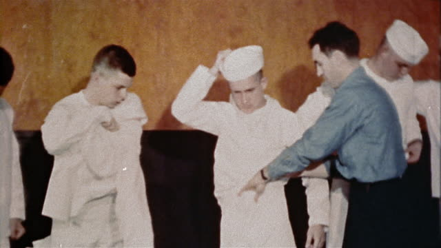 1940s US Navy recruits getting assistance with putting on new uniforms at naval training center