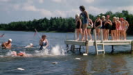 1940s wide shot girl taking her turn jumping from dock into water and swimming at summer camp
