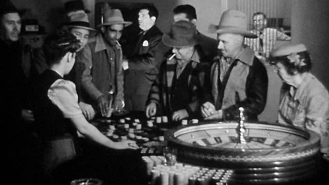 1940s wide shot group of cowboys gambling around roulette wheel at casino table