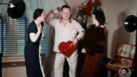 1940s wide shot man wearing pajamas dancing around with heart-shaped box of candy / 2 women watching