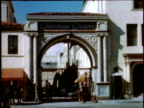 1940s WIDE SHOT pedestrians passing the Paramount Pictures gate / Hollywood, California, United States