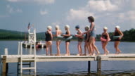 1940s wide shot swim instructor lining girls in bathing suits up on pier at summer camp