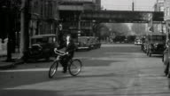 1940s wide shot teenage boy swerving bicycle toward CAM on city street / elevated train tracks in background