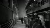 1940s wide shot uniformed guard and prisoners walking along cell block inside jail