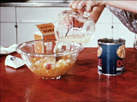 1940s woman's hands pours liquid gelatin into bowl of fruit cocktail then spoons it into can /AUDIO