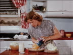 1940s zoom in housewife pours fruit salad gelatin mold from can to plate then starts slicing it / indust.