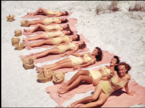 1940s/50s high angle line of women in identical swimsuits lying on towels on beach turn over onto stomachs