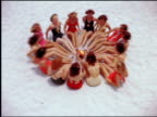 1940s/50s high angle women in swimsuits lie in circle on sand with beach ball in middle / start tossing ball