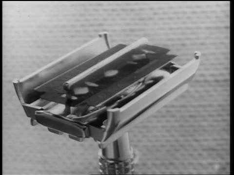 B/W 1950s ANIMATION close up razor blade inserting itself into razor