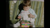1950s Baby Girl Playing with an Easter Egg Basket