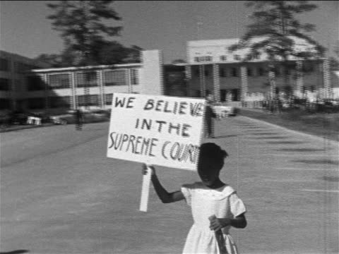 B/W 1950s Black girl carrying sign 'We Believe in the Supreme Court' on sidewalk / Texas / news