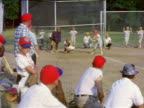 1950s boys + men in red + blue baseball caps watching boy batting in Little League game / home movie