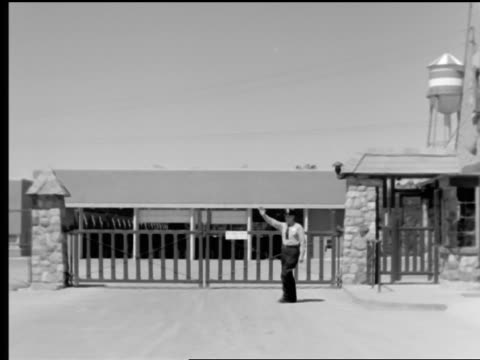 B/W 1950s car point of view to security guard stepping in front of gate holding up hand for car to stop