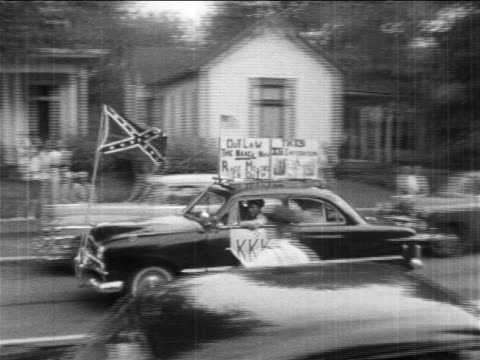 B/W 1950s PAN car with Confederate flag KKK sign driving past desgregated school / newsreel