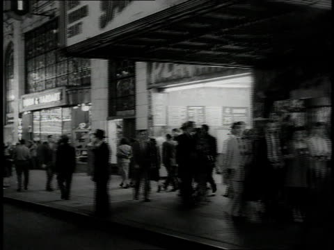 1950s WS City night scene, pedestrians walking on brightly lit street / New York City, New York, United States