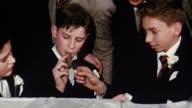 1950s close up boy lighting cigar other boy / boy smokes cigar