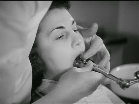 B/W 1950s close up dentist's hands cleaning woman's teeth