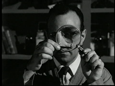 1950s close up man looking at bullet through magnifying glass / tilt down to tagged gun