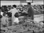 B/W 1950s couple with two children shopping in produce department of grocery store / pick up melon