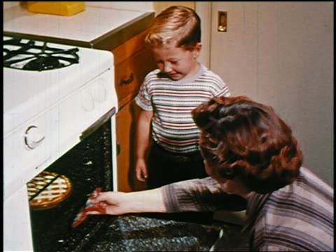 1950s excited young blond boy watching as woman pulls pie out of oven in kitchen