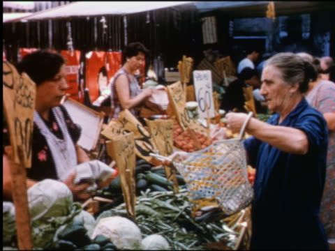 1950s female vendor putting produce into senior woman's bag at outdoor market / Venice, Italy